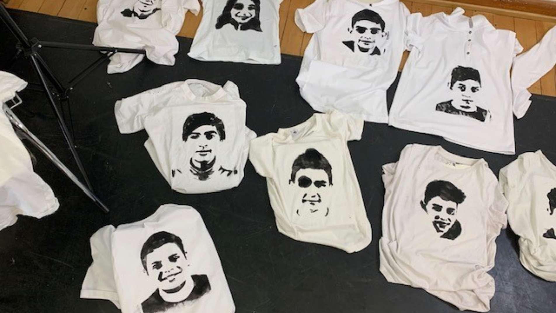 Auf dem Boden liegende, weiße T-Shirts, die in Schwarz mit Gesichtern bedruckt sind