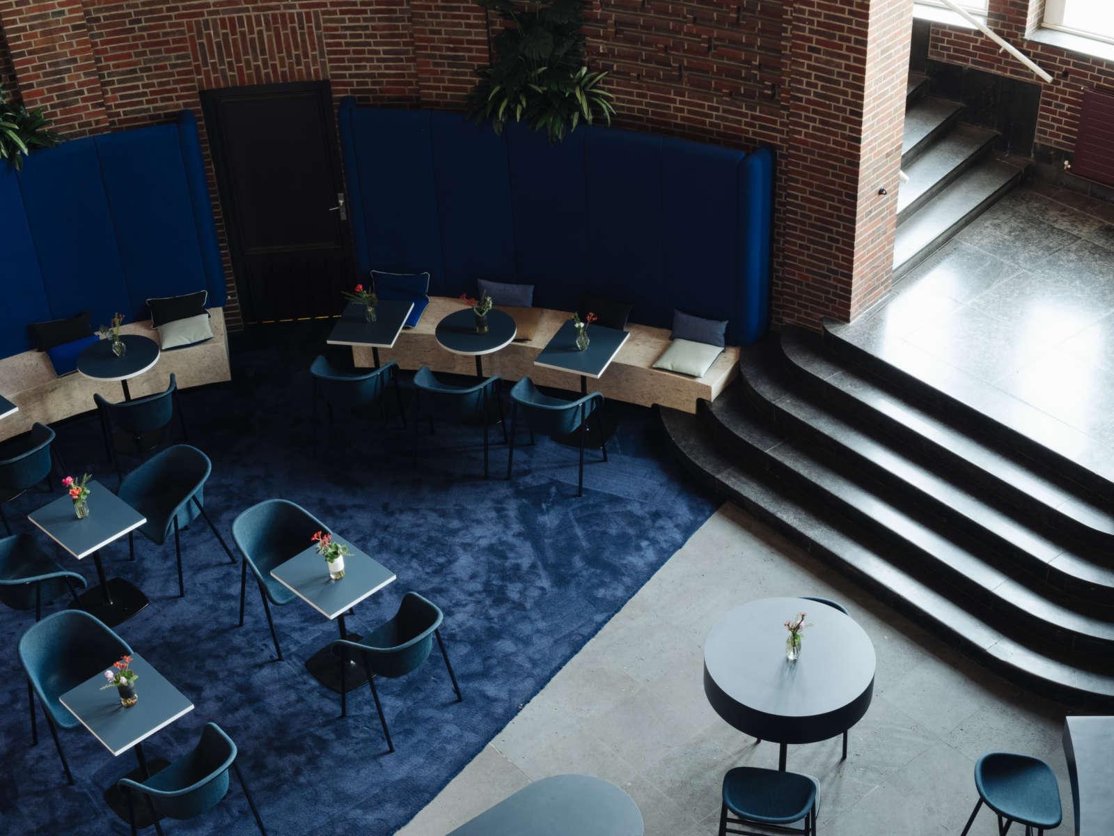 Gastronomie Pong mit mehreren blauen, mit Blumen dekorierten Tischen und blauen Stühlen auf einem blauen Teppich vor roten Backsteinwand