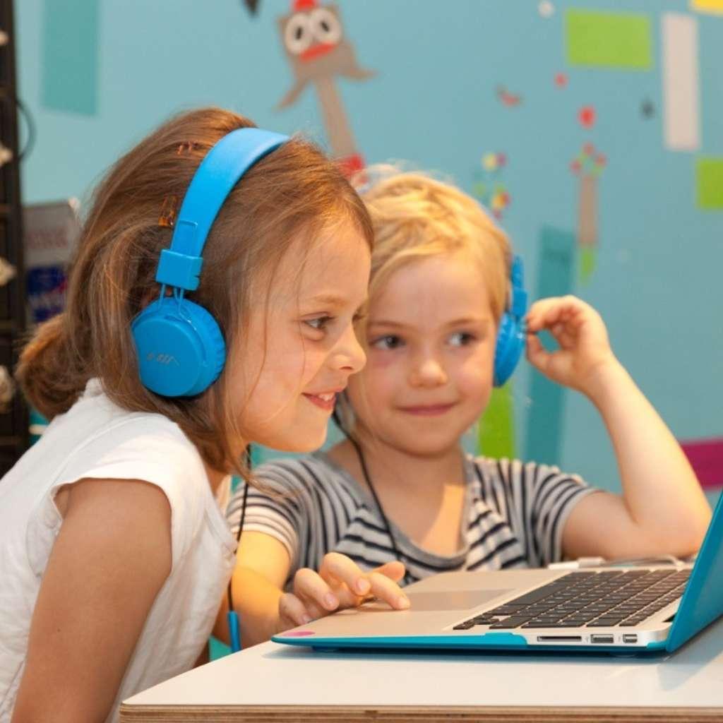 Zwei kinder sitzen vor einem Laptop mit blauer Schutzhülle und haben blaue Kopfhörer auf vor einer bunten Wand im Hintergrund