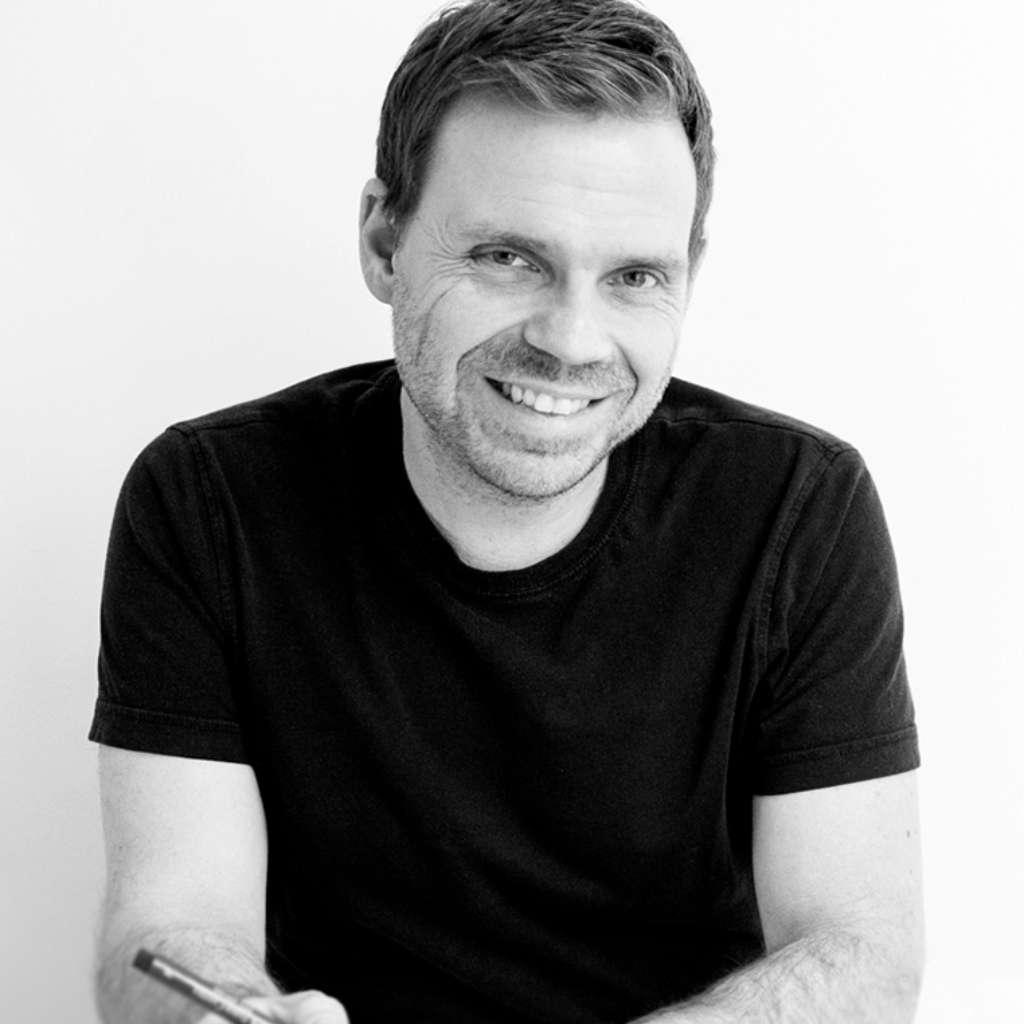 Carsten Heisterkamp an einem Tisch sitzend mit einem Stift in der Hand in Schwarz Weiß