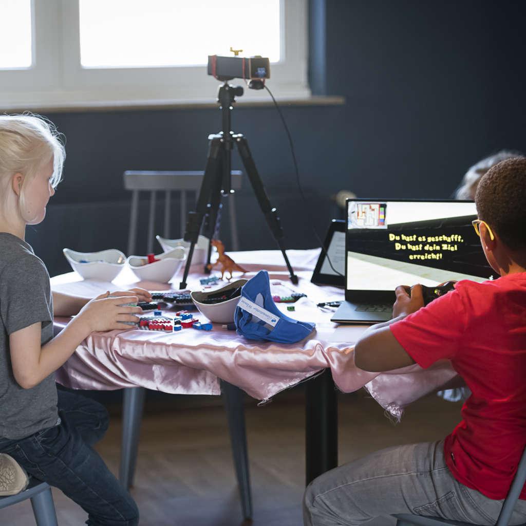 Zwei Kinder sitzen an einem Tisch auf dem ein Laptop mit geöffnetem Spiel steht sowie Legosteine und ein Stativ mit Kamera sind