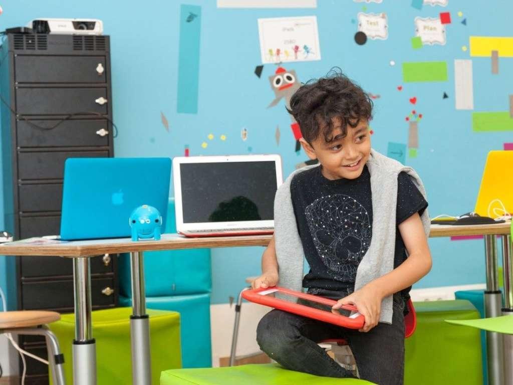 Ein kleiner Junge kniet mit einem Bein auf einem Hocker und hat ein rotes Tablet in der Hand vor einem Tisch mit Laptops und einer bunten Wand