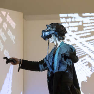 Woman with VR glasses and a controller in her hand standing in front of video projections