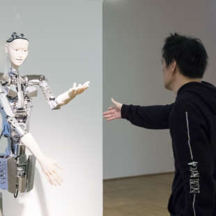 Man reaching out his hand to a robot made out of metal and wires with his hands and head looking like a human being