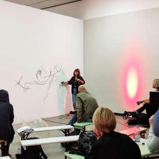 Künstlerin malt auf weißer Wand während sie von mehreren Personen, die auf Bänken sitzen, beobachtet wird