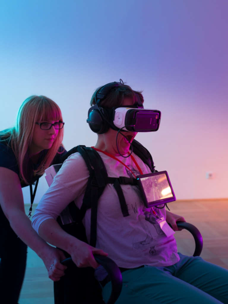 Eine Person sitzt mit einer VR Brille auf dem Kopf auf einem Bürostuhl, an dem sie sich festzuhalten versucht und wird von einer jungen Frau geschoben