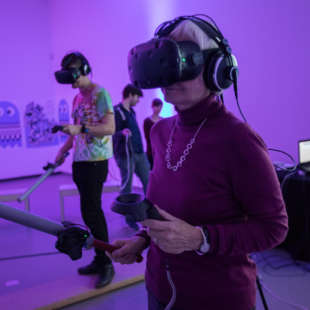 Older woman standing in purple lit room with VR glasses on her head and a controller and electronic sword in her hand