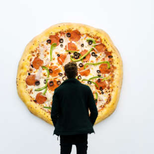 In the exhibition Pizza is God, a man stands in front of an artwork by Tom Friedman, which is a huge pizza hanging on the wall