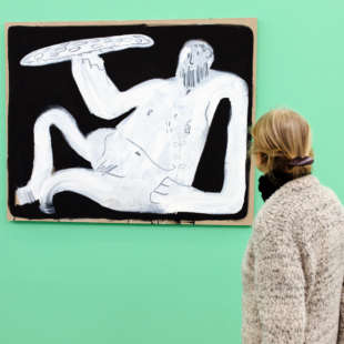 Woman watching a abstract painting of a lying man withe pizza in his hand in black and white in the exhibtion Pizza is God