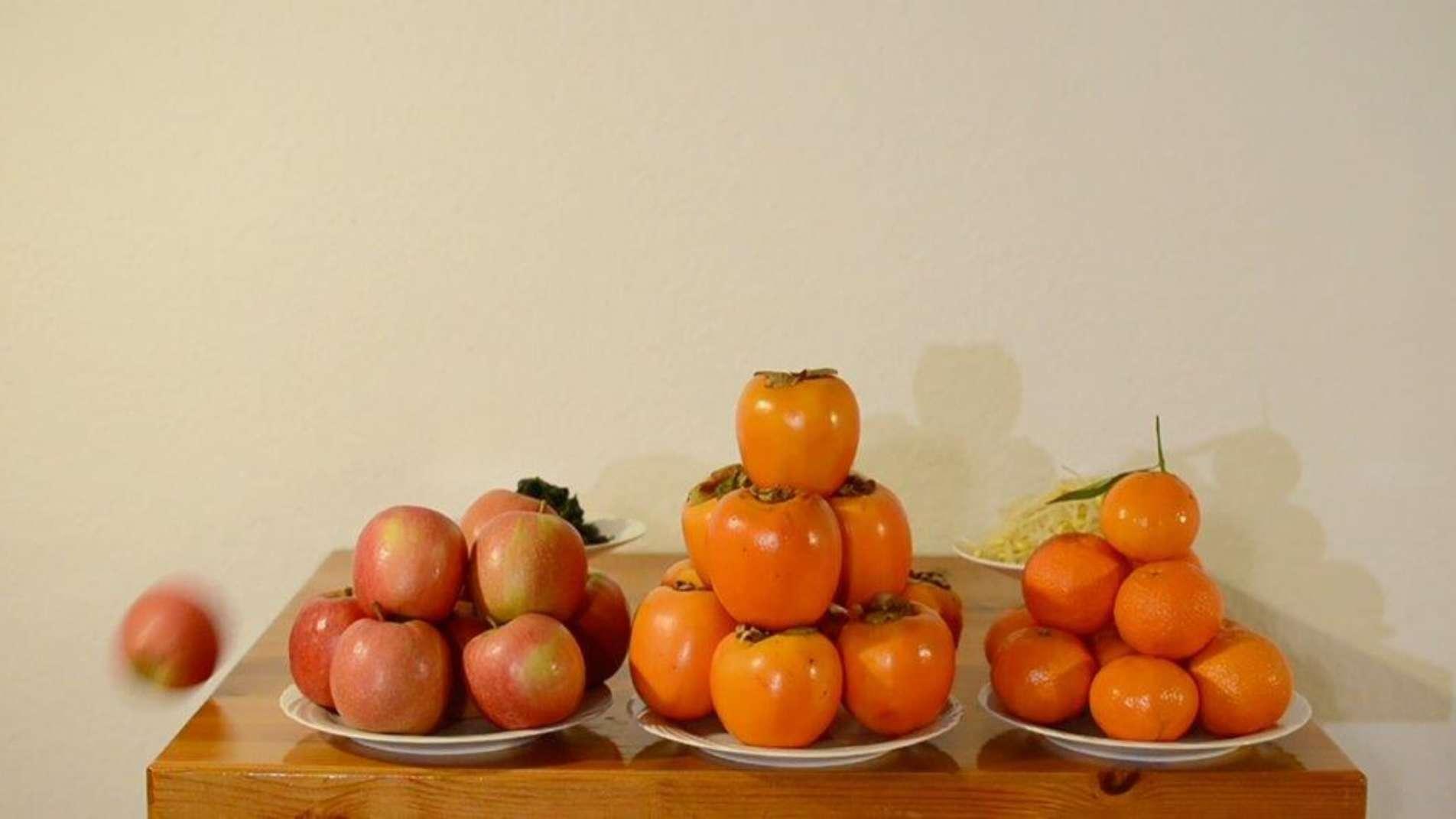Drei Teller auf einem Tisch vor einer weißen Wand mit jeweils einem Haufen aus Kakis, Orangen und Äpfeln