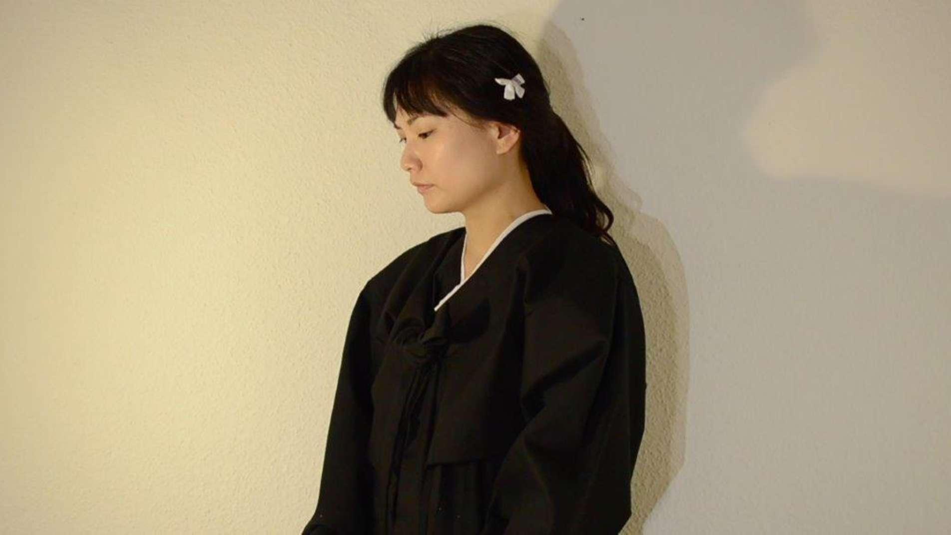 Frau mit schwarzen Haaren, die zu einem Zopf gebunden sind, und einem schwarzen Umhang, steht im Halbprofil vor einer weißen Wand