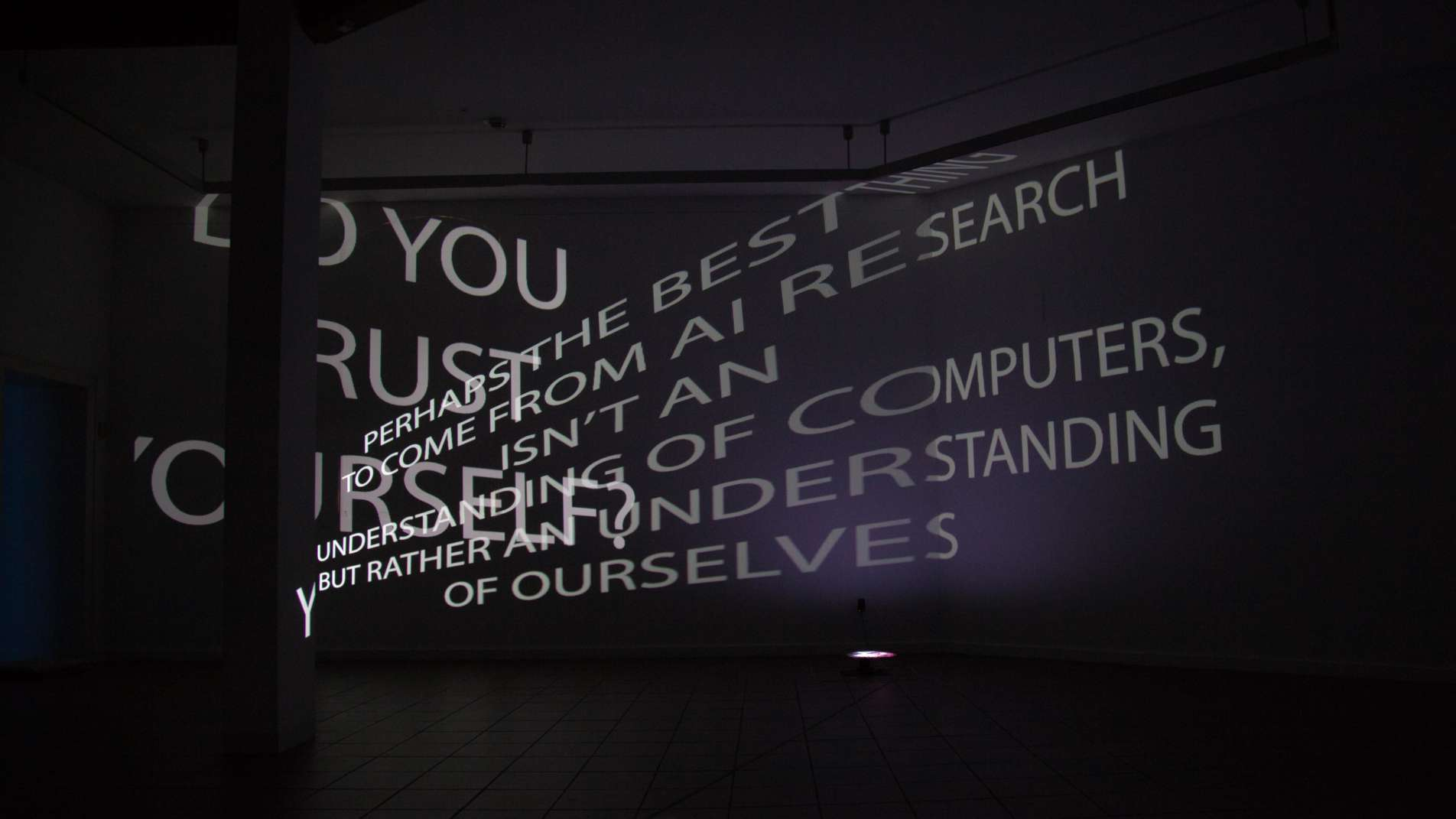 Two sentences in English are projected into a room in a dark environment