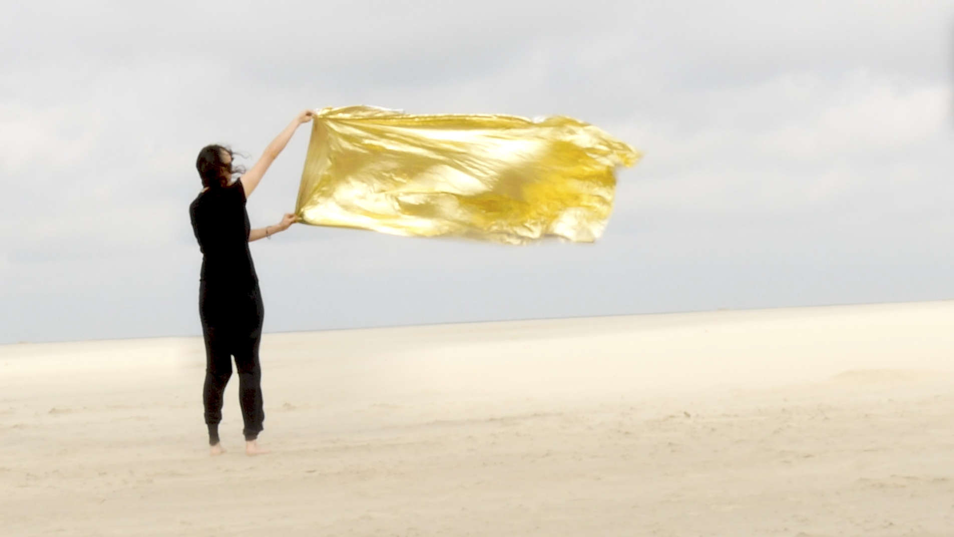 Black dressed woman stands in a desert and holds a golden cloth in the strong wind under overcast sky