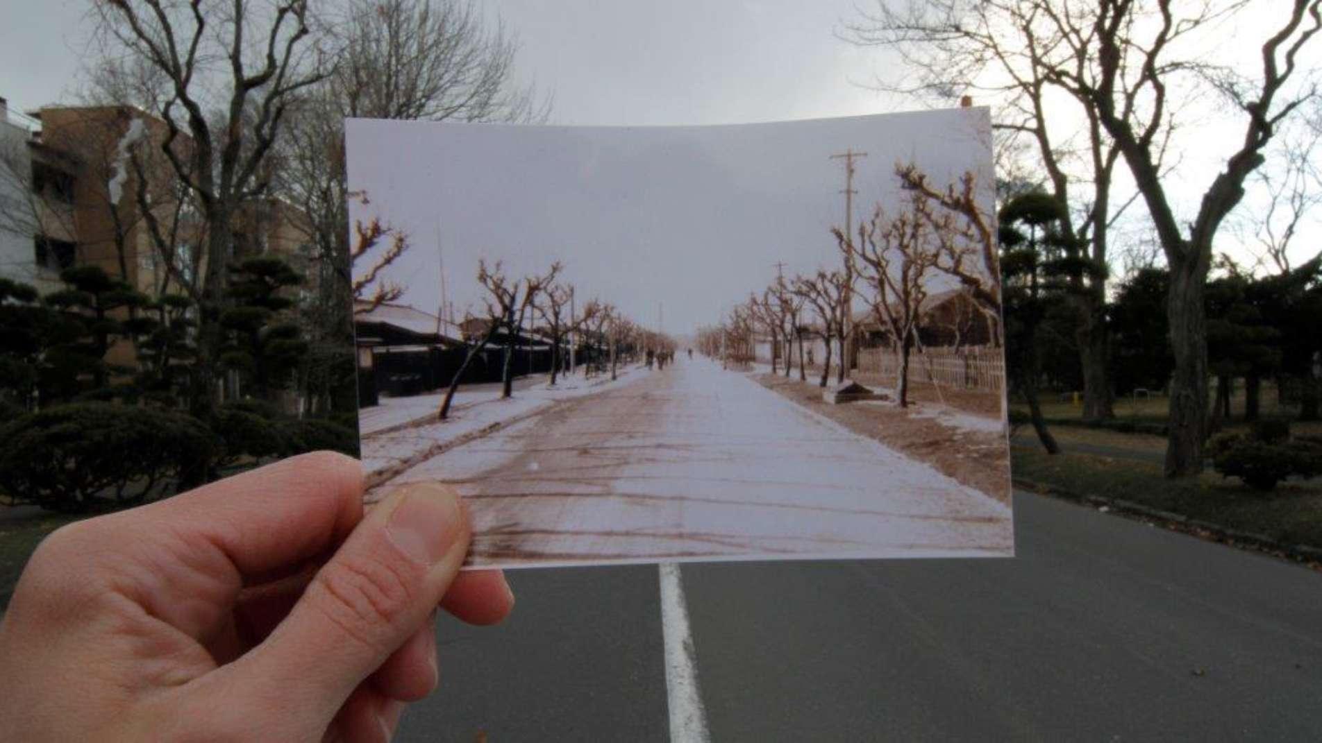Im Hintergrund eine Straße mit Landschaft an beiden Seiten, die von einem hochgehaltenen Foto von der selben Straße im Vordergrund verdeckt wird