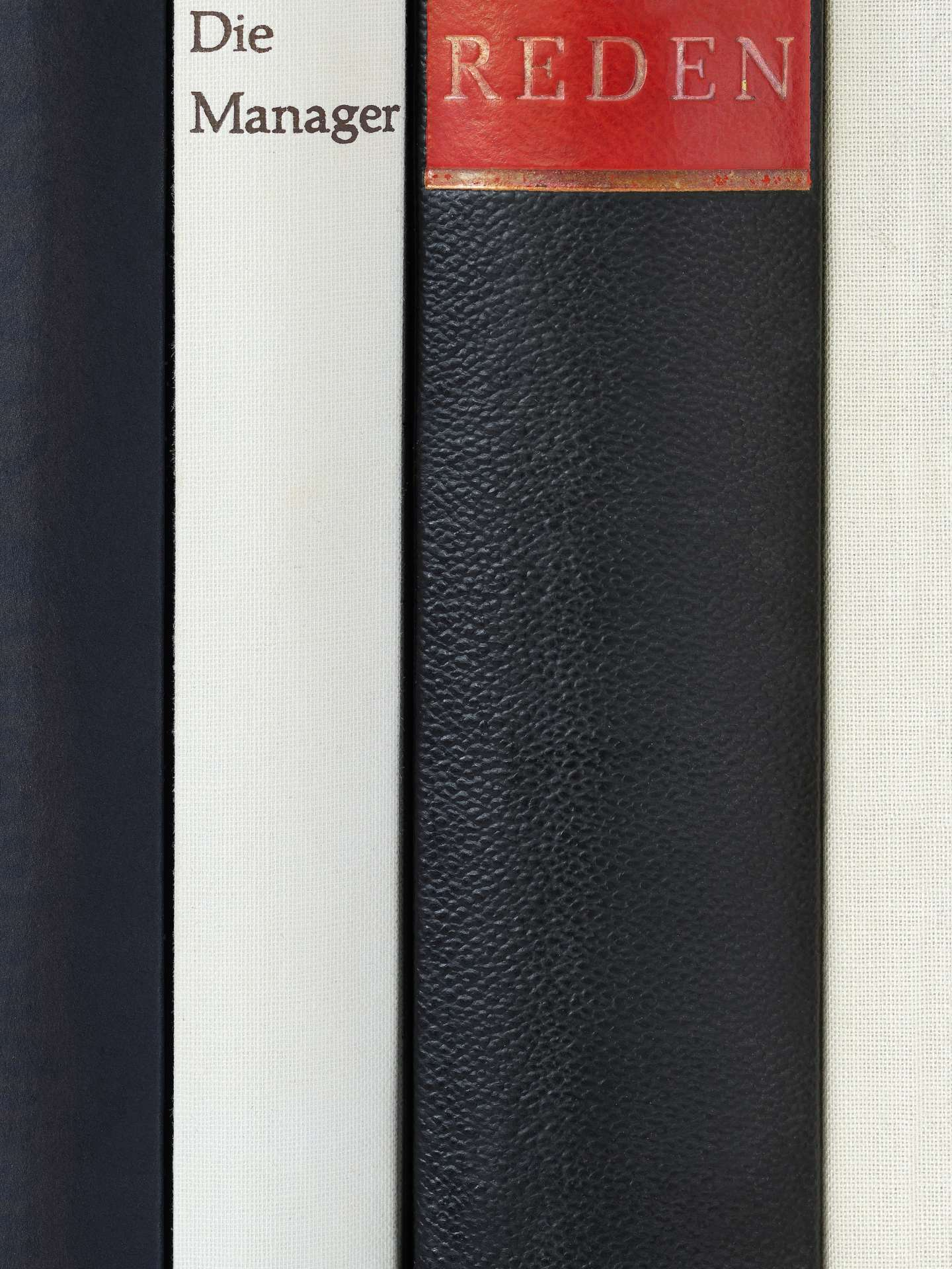 Several black and white book spines stand side by side, on which the managers and talking stands in german