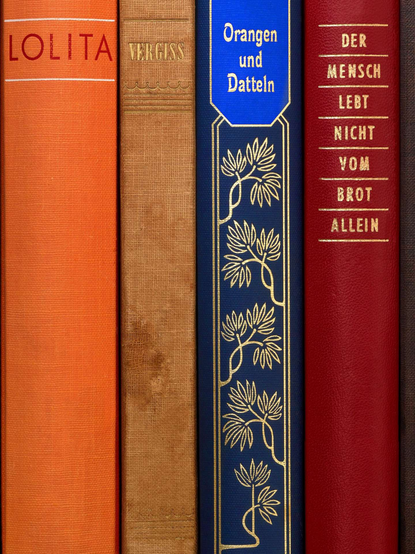 Several book spines stand side by side, on which are written Lolita, Forget, Dates and Oranges and Man does not live by bread alone in german
