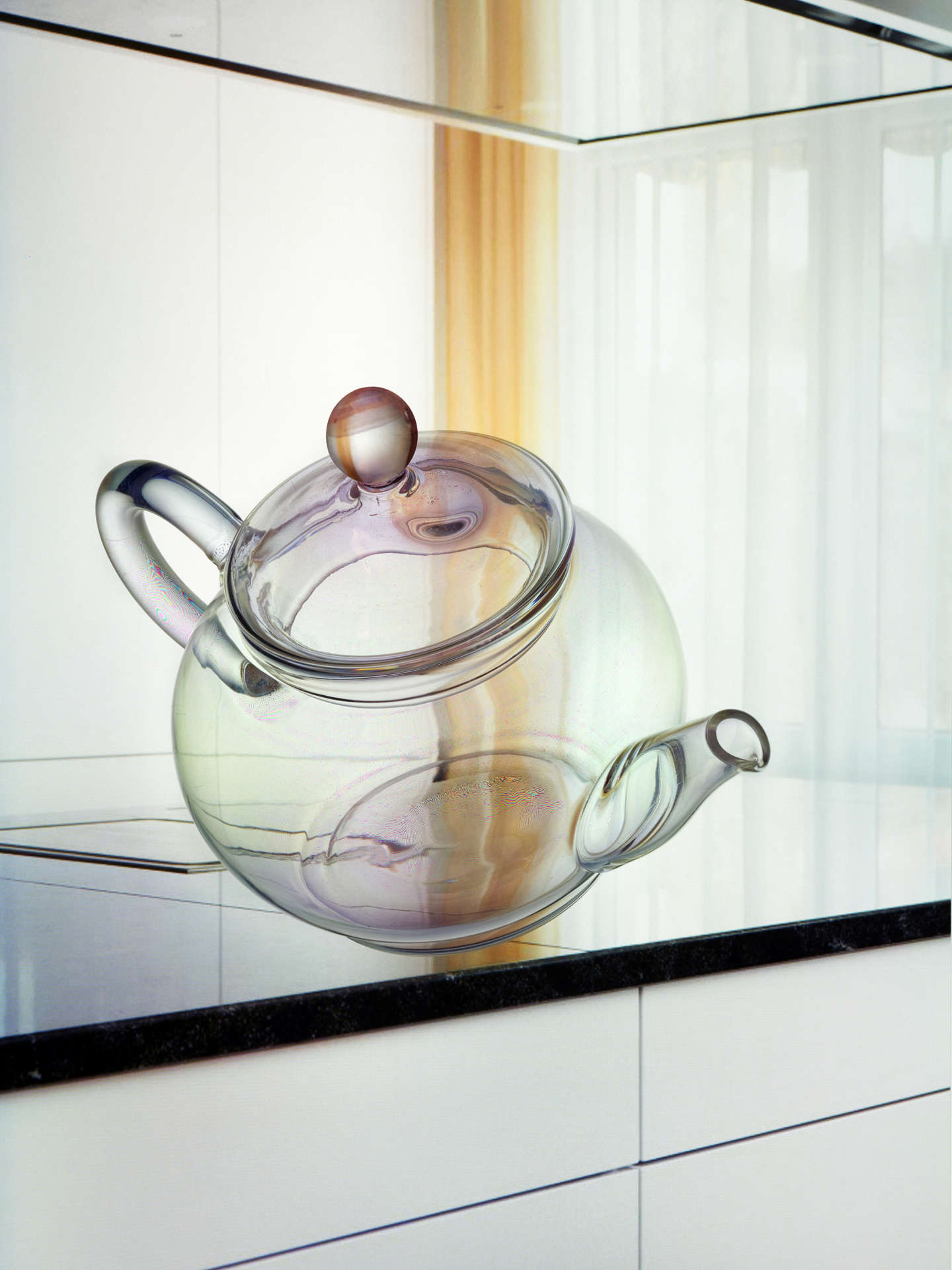 A transparent teapot made of glass falls from a white kitchen unit with a black worktop