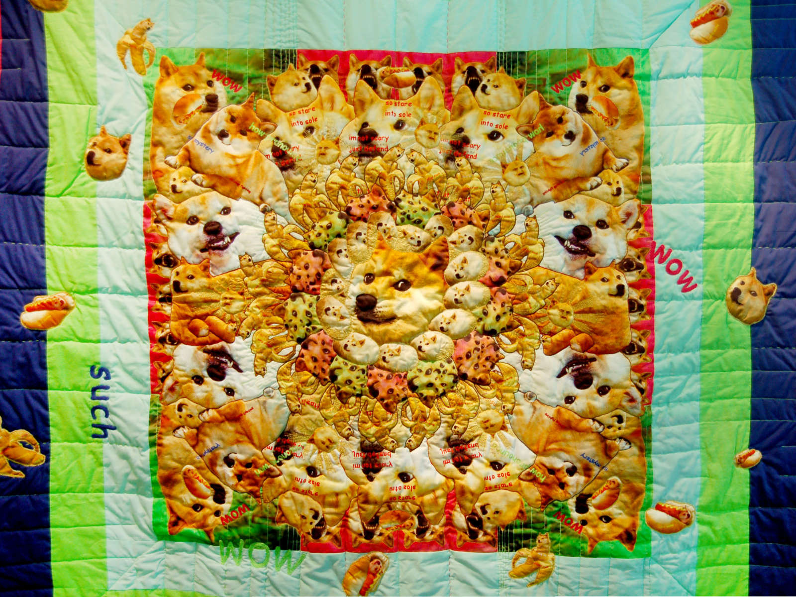 View of a colourful, quilted cotton blanket with applications of dog heads, dogs in banana peels and dogs as hot dogs