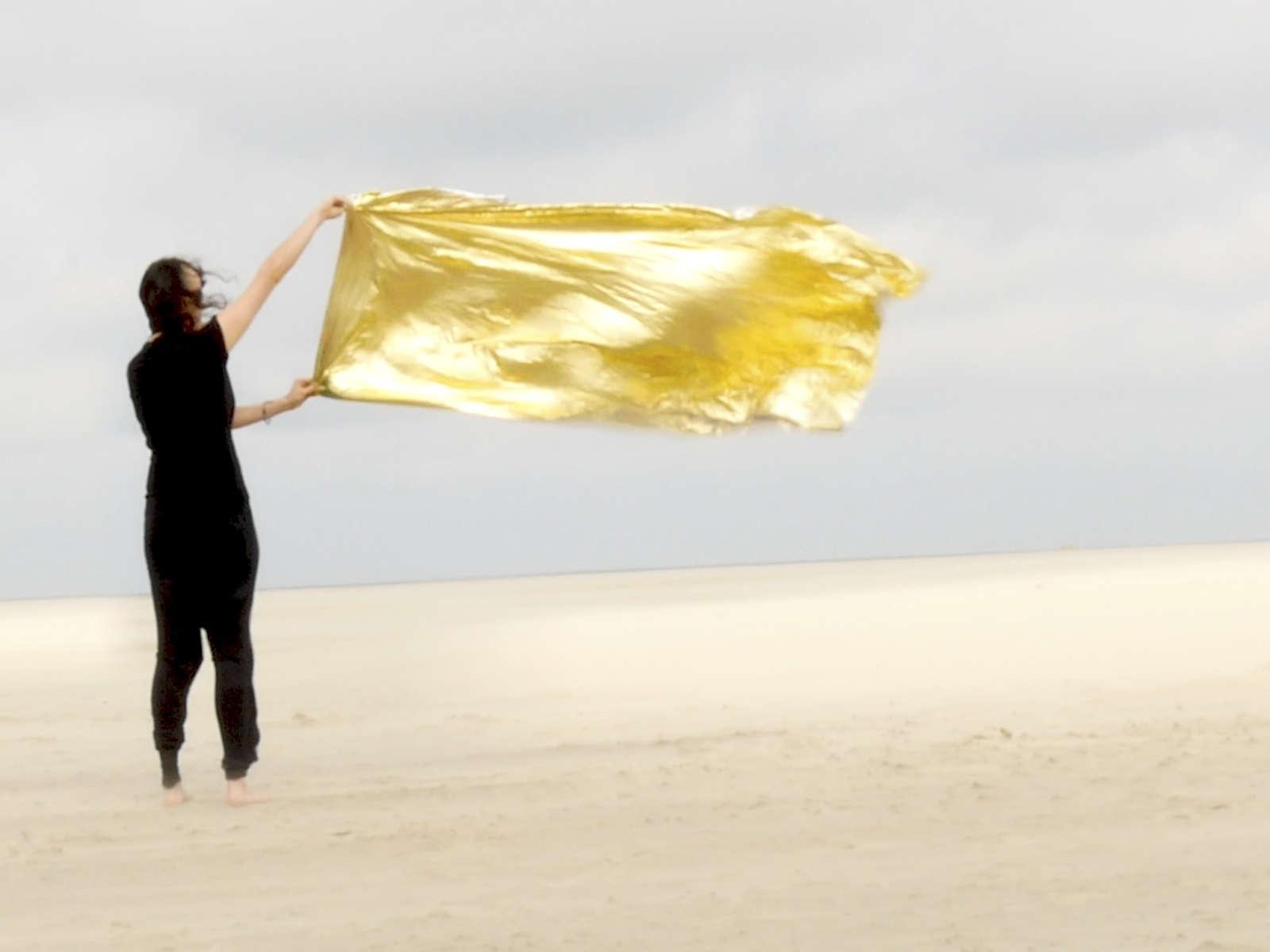 Schwarz gekleidete Frau steht in einer Wüste und hält ein goldenes Tuch in den starken Wind unter bedecktem Himmel