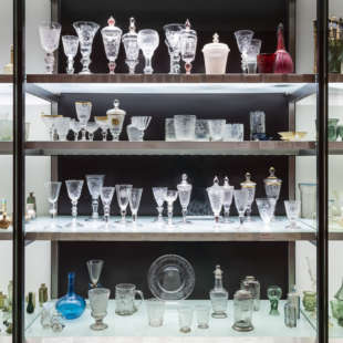 Regal mit Glasböden in dem viele bunte Gläser und Glasartefakte stehen