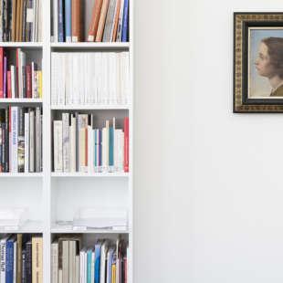 Weißes Regal gefüllt mir Büchern links und ein an der Wand hängendes Gemälde mit Porträt einer jungen Person mit langen Haaren rechts