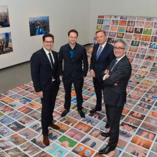 Vier Personen, unter anderem Alain Bieber, künstlerische Leiter des NRW Forums, stehen in einer Ausstellung auf einer mit Fotos beklebten Skateramp