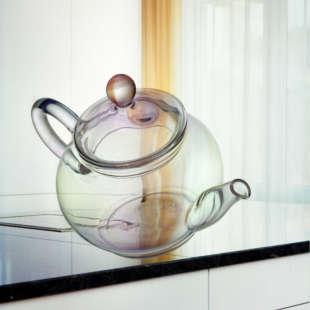 Eine durchsichtige Teekanne aus Glas fällt von einer weißen Küchenzeile mit schwarzer Arbeitsfläche