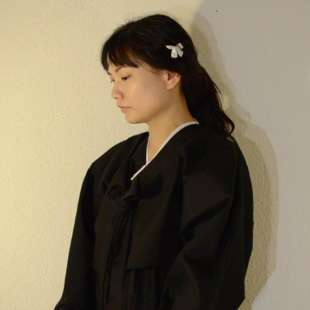 Woman with black hair tied in a braid and a black cape, standing in semi-profile in front of a white wall