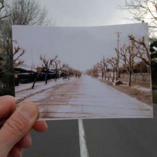 In the background, a road with landscape on both sides, which is hidden by a raised photo of the same road in the foreground