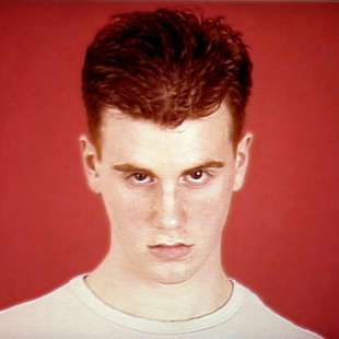 Young man with red hair and a whit t-shirt in front of a red background looking into the camera