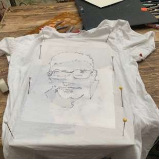 Weißes T-Shirt, dass mit einer Pappe unterlegt ist und auf dem die Konturen eines Gesichts eines Jugendlichen abgezeichnet sind