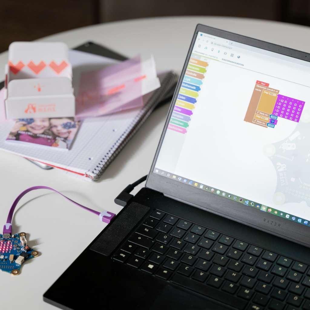 Ein aufgeklappter Laptop mit geöffnetem Codierungsprogramm, mit dem eine Platine verbunden ist steht auf einem weißen Tisch mit Unterlagen
