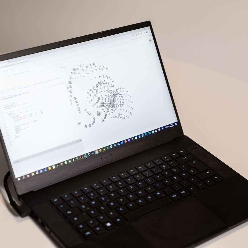 Schwarzer, aufgeklappter Laptop mit geöffnetem Codierungsprogramm
