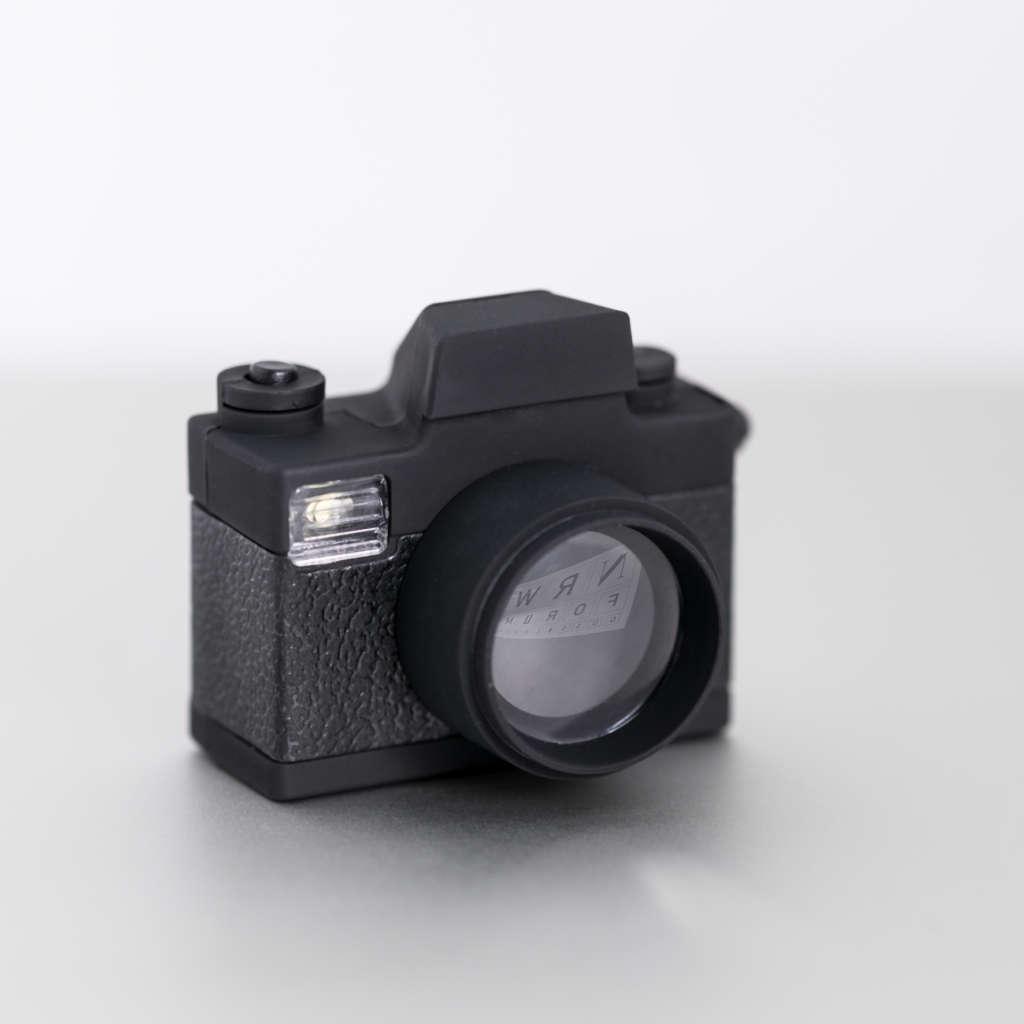 Schwarze Miniaturkamera, bei der sich das Logo des NRW Forums in der Linse spiegelt