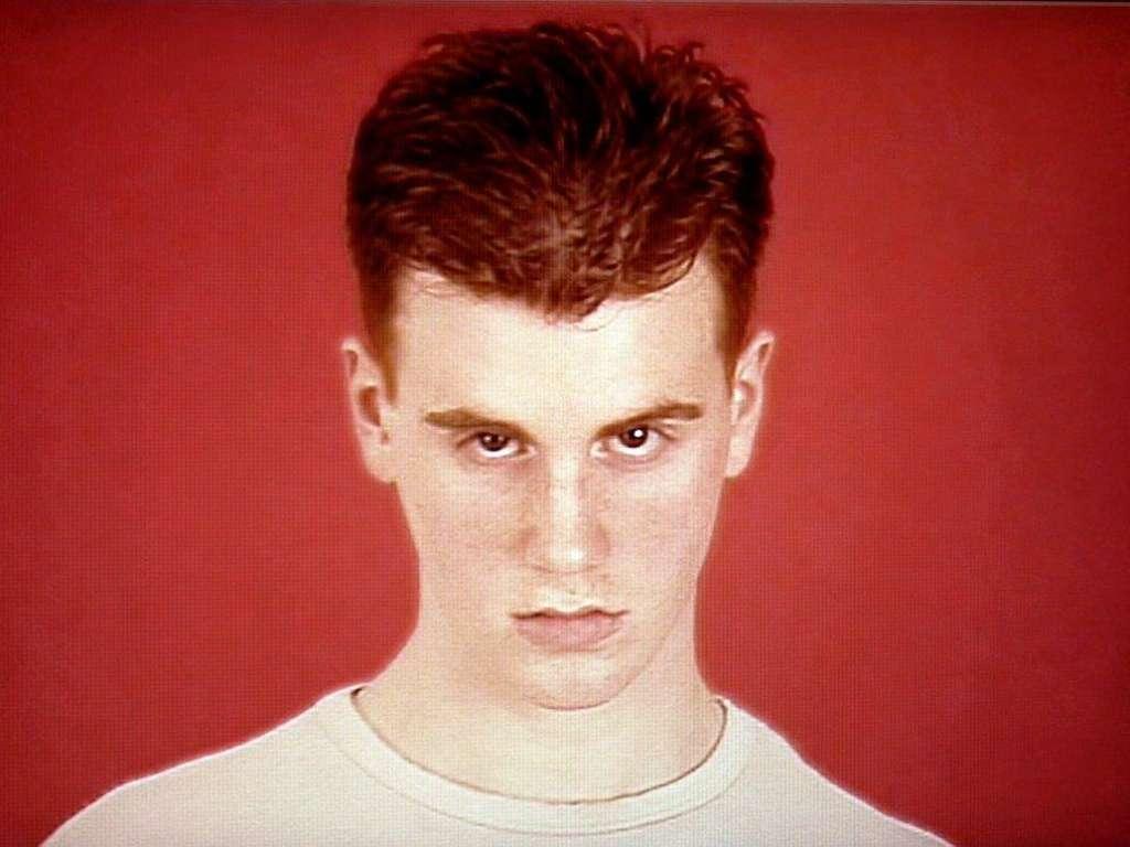 Junger Mann mit roten Haaren und weißem T-Shirt vor rotem Hintergrund mit leicht gesenktem Blick in die Kamera schauend