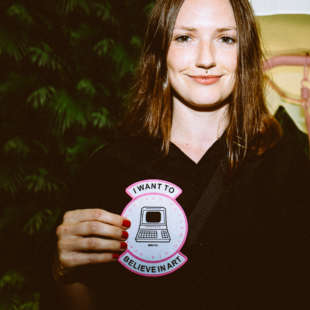 A young woman holds a badge in front of her on which is written I want to belive in art and shows a computer