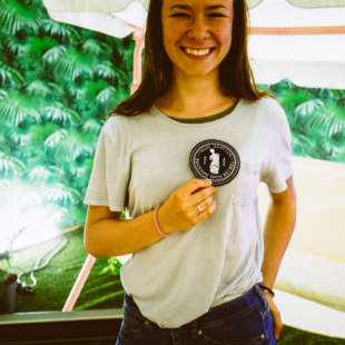 A young woman holds up a badge of the Academy of the Avantgarde and smiles