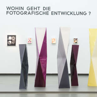 Exhibtion view of Bauhaus and photography with colorful sculptures made out of photopaper in the foreground and abstract photos in the back