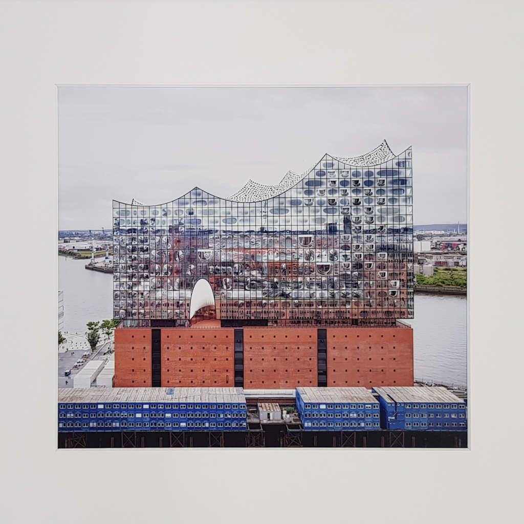 Elbphilharmonie mit blauen Containern im Vordergrund und Flusslandschaft im Hintergrund sowie Reflektion der Stadt Hamburg in der spiegelnden Fassade