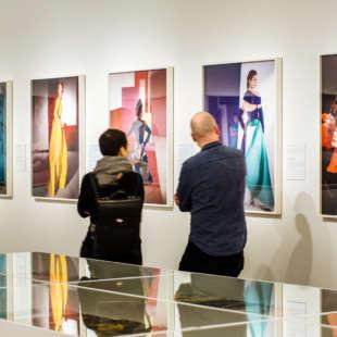 Zwei Personen schauen sich in der Ausstellung Horst Photographer of Style an der Wand hängende Fotografien an. Im Vorderungd stehen weiße Vitrienen