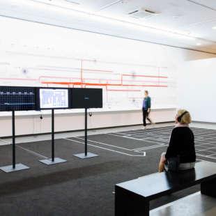 Mehrere Personen betrachten ein Kunstwerk von Forensic Architecture in der Ausstellung Im Zweifel für den Zweifel