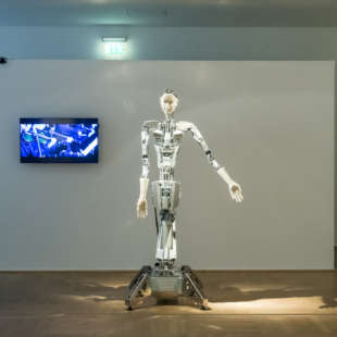 In the exhibition Körperwende, a robot stands in front of a white wall with a screen hanging on it