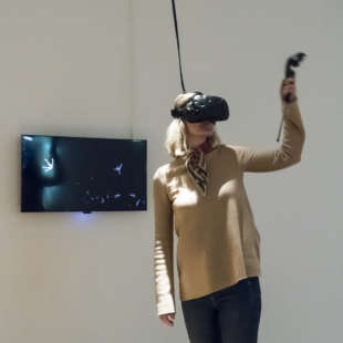 A woman wearing VR glasses in the exhibition Körperwende