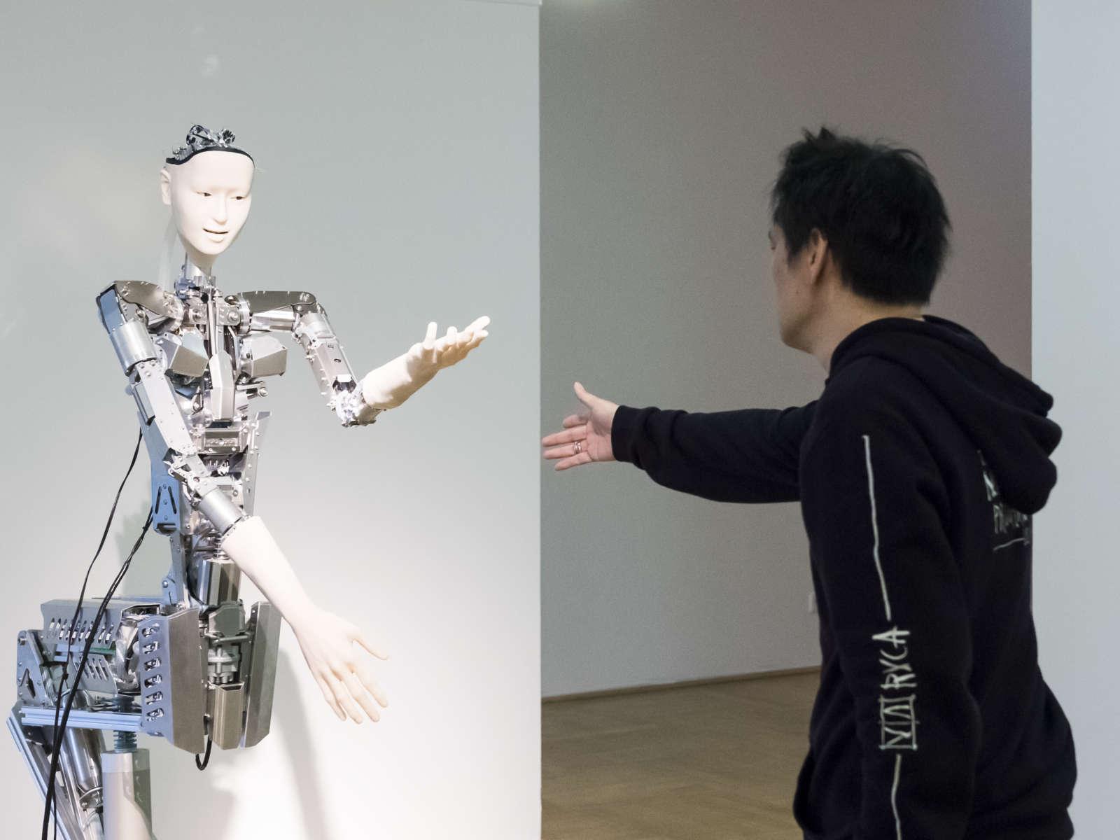 Ein schwarz gekleideter Mann reicht einem Roboter die Hand in der Ausstellung Körperwende