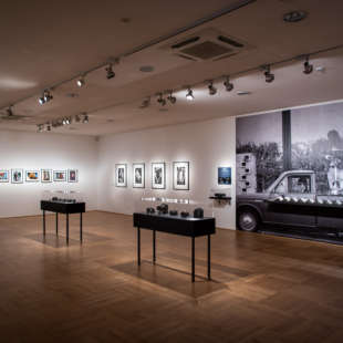 Exhibition view of the exhibition 100 Years of Nikon with several small photographs, a large photo wallpaper and two black vitriae