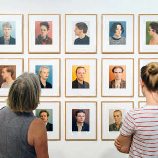 Two women view portraits of the artist Thomas Ruff in the exhibition Made in Düsseldorf Number One