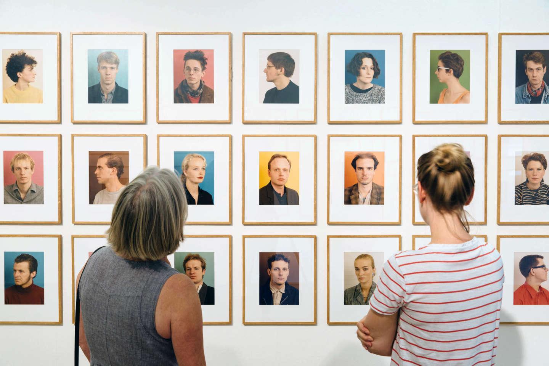 Zwei Frauen betrachten in der Ausstellung Made in Düsseldorf Nummer eins Porträtaufnahmen des Künstlers Thomas Ruff
