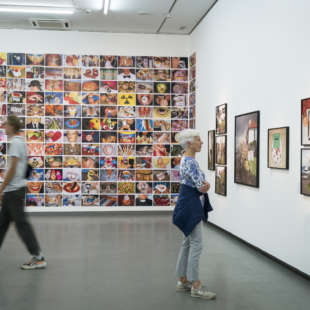 Two people are looking at works of art in the Martin Parr retrospective