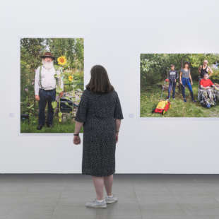 A woman looks at pictures of allotment gardeners by Martin Parr