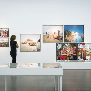 A person in the Martin Parr retrospective looks at pictures of the photographer